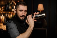 Male bartender with shaker in his hands. Male bartender with beard holding shaker in his hands stock photos