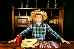 Male bartender in a sombrero standing at the counter, bottle of. Tequila and a plate with snacks on it in Mexican pub stock photography