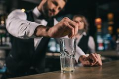 male bartender squeezing out lemon juice into glass stock photography