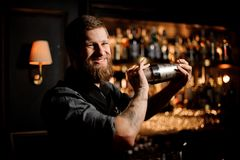 Male bartender using shaker to pour alcohol cocktail. Smiling male bartender using steel shaker to pour alcohol cocktail stock photography
