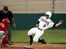 Male Baseball Player in Wolves 9 Jersey Sliding in Front of Male in Catchers Uniform Holding Baseball on Brown Mitt Stock Photos