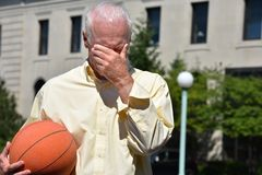 Male Basketball Coach And Depression With Basketball. A retired senior adult male stock photos