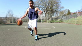 Male basketball player dribbling and scoring stock video
