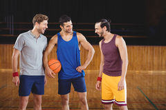Male basketball players laughing in basketball court. Happy male basketball players laughing in basketball court Royalty Free Stock Photos