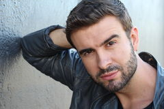 Male with a beard and mustache, dressing in a leather jacket and v-neck tee, is leaning against the wall, thinking outside Stock Images