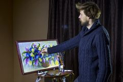 Male bearded artist in a dark sweater draws an artistic brush painting flowers still life in studio. A man bearded artist in a dark sweater draws an artistic Stock Image