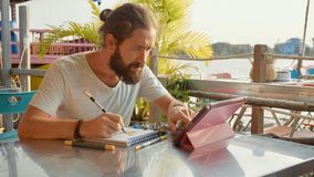 Male designer draw sketches in open air riverside cafe. Male bearded designer draw sketches in open air riverside cafe and using the tablet Stock Images