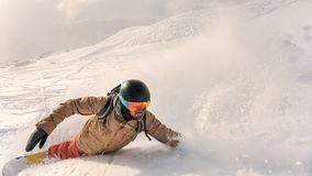 Male bearded snowboarder in sportswear and helmet riding down th. E powder snow hill on the sunny day Stock Photos