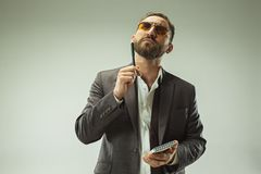 Male beauty concept. Portrait of a fashionable young man with stylish haircut wearing trendy suit posing over gray. Male beauty concept. Portrait of a Royalty Free Stock Photography