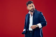 Male beauty concept. Portrait of a fashionable young man with stylish haircut wearing trendy suit posing over red. Background. Perfect hair. Elegant italian Royalty Free Stock Photography