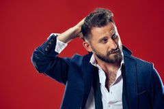 Male beauty concept. Portrait of a fashionable young man with stylish haircut wearing trendy suit posing over red. Background. Perfect hair. Elegant italian Stock Photos