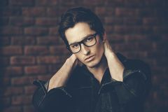 Guy in spectacles. Male beauty, fashion. Handsome young man posing in spectacles and black denim jacket by the brick wall. Hair styling Royalty Free Stock Images