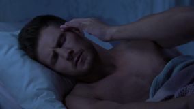 Male in bed suffering from migraine, worried about problems, lack of sleep. Stock footage stock video