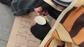 Male beggar counting money and putting in paper cup, sadness and poverty. Stock footage stock video footage