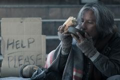 Homeless man on the stair of the walkway street in the city eating bread and milk form kindness people give him. Male Beggar, Homeless man on the stair of the stock image