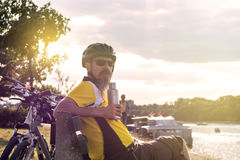 Male bicycle rider sitting on the bench Stock Images