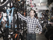 Male in bicycle shop chooses for himself sports bike Stock Image