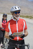 Male Bicyclist Holding Map With Woman In The Background Royalty Free Stock Image