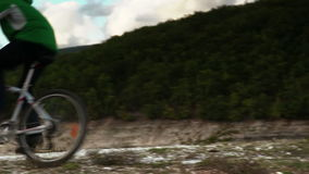 Male bicyclist rides a mountain bicycle down the hill near the lake in autumn stock footage