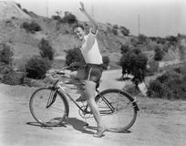 Male bicyclist waving. (All persons depicted are no longer living and no estate exists. Supplier grants that there will be no model release issues stock image