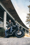 Male biker in a leather jacket on a motorcycle near the bridge Stock Images