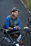 Male biker in pain holding his injured leg Royalty Free Stock Photo