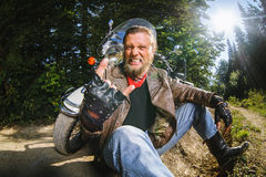 Male biker sitting on dirt road near motorcycle Royalty Free Stock Photography