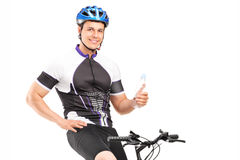 Male biker sitting on his bike and holding a bottle Royalty Free Stock Image