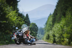 Male biker sitting on road near motorcycle. Handsome biker with beard and long hair sitting next to his custom made cruiser motorcycle on an open road. Guy is Stock Photos
