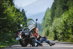 Male biker sitting on road near motorcycle. Handsome biker with beard and long hair sitting next to a traveler motorcycle on an open road. Guy is wearing leather Royalty Free Stock Photos