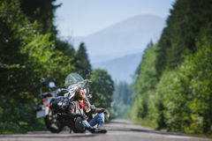 Male biker sitting on road near motorcycle. Handsome biker with beard and long hair sitting next to a traveler motorcycle on an open road looking to the sun Royalty Free Stock Photos