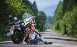 Male biker sitting on road near motorcycle. Handsome biker with beard and long hair sitting next to a traveler motorcycle on an open road and smilling. Guy is Royalty Free Stock Photos