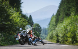 Male biker sitting on road near motorcycle. Handsome man with beard and long hair sitting next to a traveler motorcycle on an open road. Guy is wearing leather Stock Photos