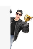 Male biker standing behind blank panel and holding a trophy Royalty Free Stock Photo
