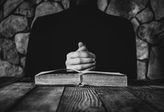 Male in black clothes in front of an old open book Royalty Free Stock Photography