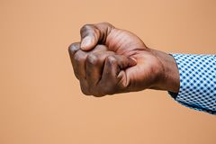 Male black fist  on brown background. African american clenched hand, gesturing up Royalty Free Stock Photography