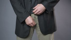 Male in black jacket pulling his pants zipper, embarrassment, man's health