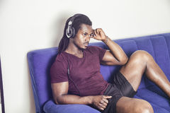 Male black man listening to music on sofa. Handsome black muscular bodybuilder man listening to music with headphones while sitting on couch Stock Photos
