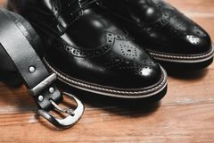 Male black shoes with belt. Stylish men`s accessories on the wooden background Stock Photography