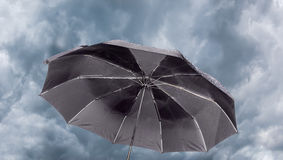 Male black umbrella against the background of a stormy sky Royalty Free Stock Images