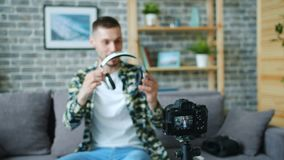 Male blogger recording video about headphones talking looking at camera. Male blogger is recording video about modern headphones talking looking at camera stock video