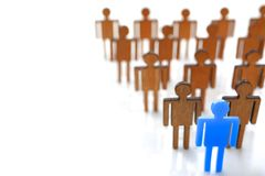 Male blue plastic toy businessman silhouette. Wooden crowd figure background closeup. Manipulate work recruitment transfer labour inspectorate experience royalty free stock photos
