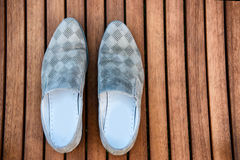 Male blue shoes over the wooden table. Male light blue shoes over the wooden table Royalty Free Stock Photos
