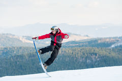 Male boarder on his snowboard at winer resort. Male boarder jumping on his snowboard and taking his for the edge on top of a mountain against the backdrop of Stock Photos
