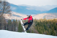 Male boarder on his snowboard at winer resort. Male boarder jumping on his snowboard and taking his for the edge on top of a mountain against the backdrop of Royalty Free Stock Photos