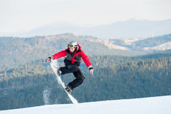 Male boarder on his snowboard at winer resort. Man boarder jumping on his snowboard and taking his for the edge on top of a mountain against the backdrop of Stock Photos