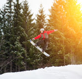Male boarder jumping and keeps one hand on the snowboard. Over the slope in winter with snowy slope and snow-covered firs in background, extreme sport Stock Photos