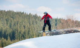 Male boarder slides down over a hurdle. Male boarder on his snowboard slides down over a hurdle in winter day with forest in the distance on background Royalty Free Stock Images