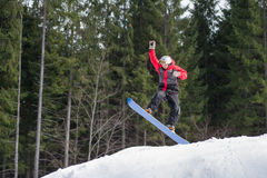 Male boarder on the snowboard jumping over the slope Royalty Free Stock Photos