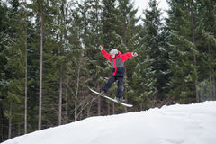 Male boarder on the snowboard jumping over the slope Royalty Free Stock Photography